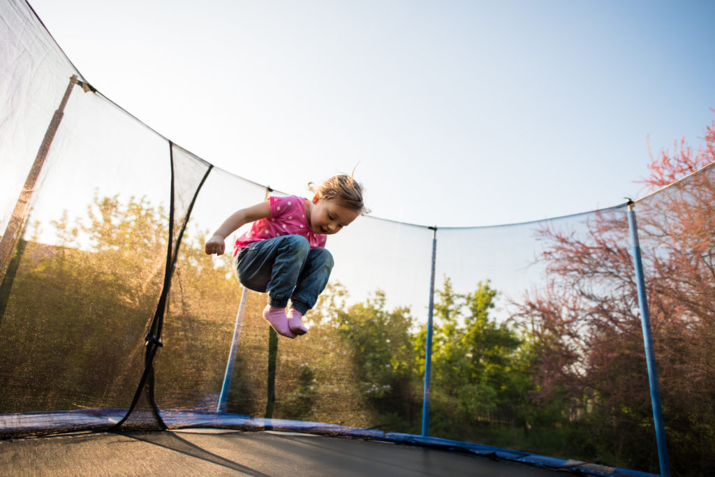 little girl jumping on trampoline in backyard