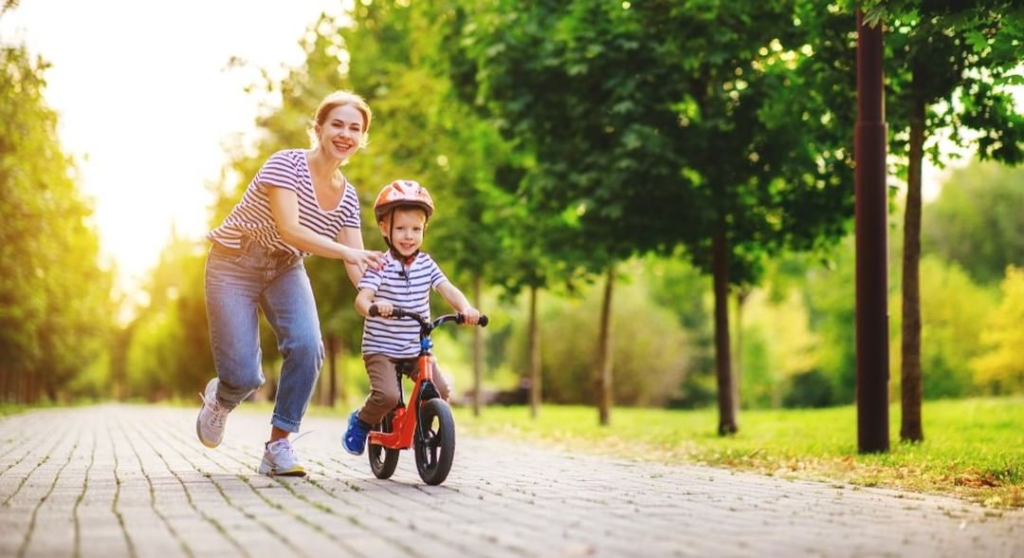 mom helping son on balance bike
