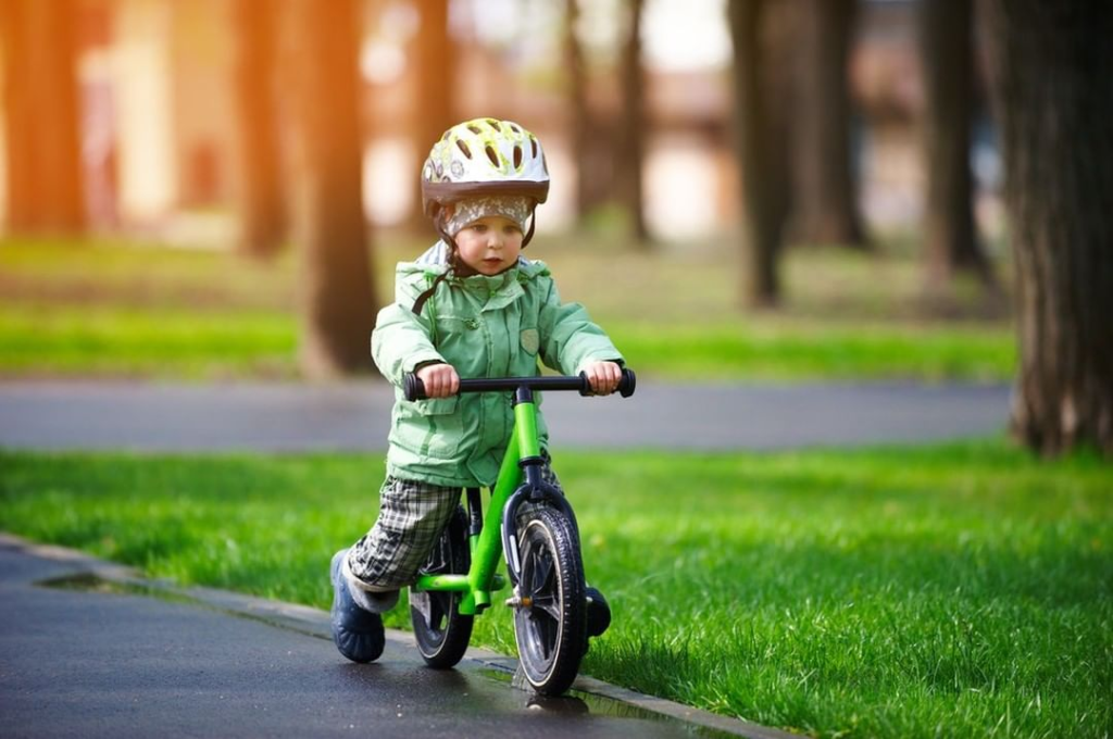 young boy riding balance bike with helmet on